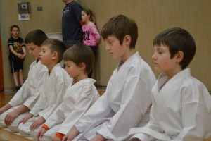 Young members meditate after karate practice.